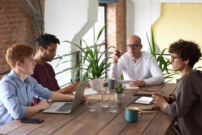Team von Mitarbeitern sitzt an einem Tisch